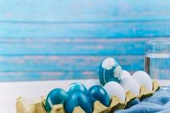 Lyckliga easter, det organiska blåa anseendet för det easter ägget på de vita färgäggen väntar på målning, easter feriegarneringa Arkivbild