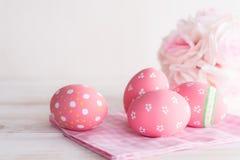 Lyckliga easter! Färgrikt av påskägg med rosa och vit cheesecloth på träbakgrund arkivfoton