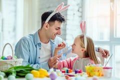 Lyckliga easter! Farsan och hans lilla dotter har tillsammans gyckel, medan förbereda sig för påskferier På tabellen är en korg m arkivbilder