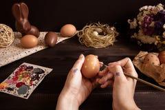 lyckliga easter Kvinnlign räcker att måla det easter ägget på trätabellen Royaltyfria Foton