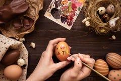 lyckliga easter Kvinnlign räcker att måla det easter ägget på trätabellen Royaltyfria Bilder