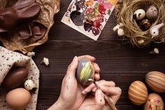 lyckliga easter Kvinnlign räcker att måla det easter ägget på trätabellen Arkivbild