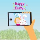 Lyckliga easter lurar selfie med kanin på den smarta telefonen Royaltyfri Bild