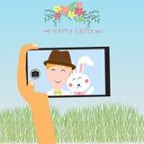 Lyckliga easter lurar selfie med kanin på den smarta telefonen Fotografering för Bildbyråer