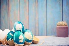 Lyckliga easter, organiska blåa easter ägg med vita färgägg väntar på målning, easter feriegarneringar Arkivfoto