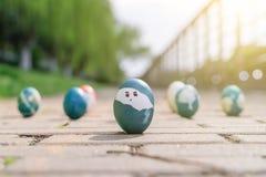 Lyckliga easter, organiska easter för gullig pojke som ägg målar framsidan på ägget, easter feriegarneringar, easter begreppsbakg Fotografering för Bildbyråer