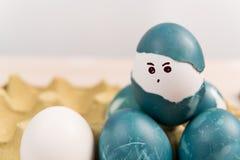 Lyckliga easter, organiska easter för gullig pojke som ägg målar framsidan på ägget, easter feriegarneringar, easter begreppsbakg Arkivbild