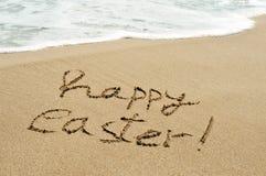 Lyckliga easter som är skriftlig i sanden av en strand royaltyfri bild