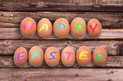 Lyckliga easter som är skriftlig på ägg på träplankor Arkivfoto