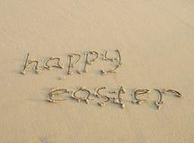 Lyckliga easter som är skriftlig på en sand arkivbild