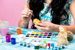 Lyckliga easter! Stäng sig upp av nätta ägg för kvinnamålningpåsken Lycklig familj som förbereder sig för påsk arkivfoto