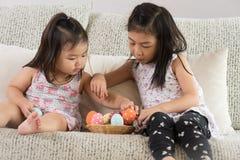 Lyckliga easter! Två gulliga lilla barn som sitter på soffan med påskägg i redet eller korgen fotografering för bildbyråer