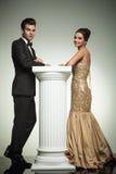 Lyckliga eleganta par som lutar ona-kolonnen Arkivfoton