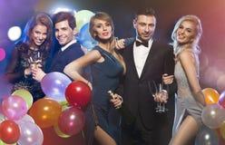 Lyckliga eleganta vänner på partiet royaltyfria foton