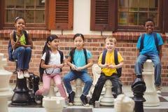 Lyckliga elever som sitter på jätte- schackstycken Royaltyfri Foto