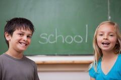 Lyckliga elever som tillsammans poserar Royaltyfri Bild