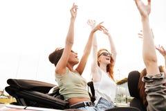 Lyckliga emotionella fyra vänner för unga kvinnor som sitter i bil royaltyfria foton