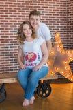Lyckliga förälder-till-är par som ser ett gulligt rött, behandla som ett barn skor för deras ofödda barn, inomhus studiostående Arkivfoton