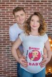 Lyckliga förälder-till-är par som ser ett gulligt rött, behandla som ett barn skor för deras ofödda barn, inomhus studiostående Royaltyfri Bild