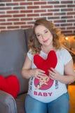 Lyckliga förälder-till-är par som ser ett gulligt rött, behandla som ett barn skor för deras ofödda barn, inomhus studiostående Arkivbilder
