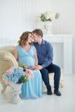 Lyckliga förälder-till-är par som ser ett gulligt rött, behandla som ett barn skor för deras ofödda barn, inomhus studiostående Royaltyfria Bilder