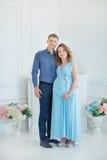 Lyckliga förälder-till-är par som ser ett gulligt rött, behandla som ett barn skor för deras ofödda barn, inomhus studiostående Royaltyfri Foto