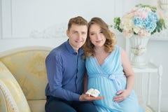 Lyckliga förälder-till-är par som ser ett gulligt rött, behandla som ett barn skor för deras ofödda barn, inomhus studiostående Arkivfoto