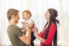 Lyckliga föräldrar fadern och modern som spelar med, behandla som ett barn sonen på i morgonen på fönsterbakgrund Gladlynt u royaltyfria bilder
