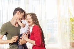 Lyckliga föräldrar fadern och modern som spelar med, behandla som ett barn sonen på i morgonen på fönsterbakgrund Gladlynt u royaltyfri fotografi