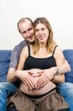 Lyckliga föräldrar gör hjärtatecknet på gravida kvinnans buk på soffan Arkivfoton