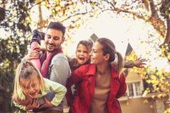 Lyckliga föräldrar har lek med döttrar På flyttningen royaltyfri foto