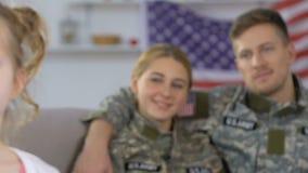 Lyckliga föräldrar i den militära likformign som ser dottern, amerikansk nationell stolthet stock video