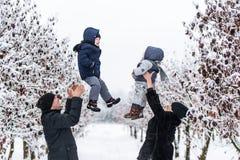 Lyckliga föräldrar kastar behandla som ett barn upp sonen, och flickan i vinter parkerar utomhus- Royaltyfri Foto