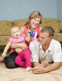 Lyckliga föräldrar med behandla som ett barn Royaltyfri Bild