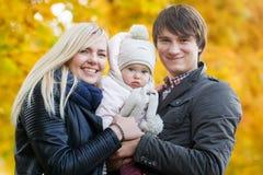Lyckliga föräldrar med den lilla dottern på bakgrund av höstskogen Arkivfoto