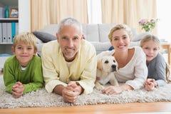 Lyckliga föräldrar med deras barn och valp på golv Royaltyfria Bilder