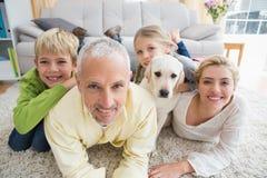 Lyckliga föräldrar med deras barn och valp på golv Arkivbild