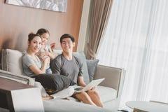 Lyckliga föräldrar med dottern som använder bärbara datorn i vardagsrum Fotografering för Bildbyråer