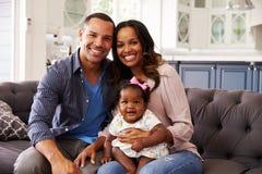 Lyckliga föräldrar med ett sammanträde för behandla som ett barnflicka på mumï¿ ½ s knäa arkivfoto