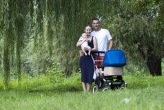 Lyckliga föräldrar med hans unga son i sommar parkerar royaltyfri foto