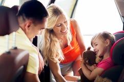 Lyckliga föräldrar med lilla flickan behandla som ett barn in bilsätet Fotografering för Bildbyråer