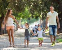 Lyckliga föräldrar med små barn som in går, parkerar royaltyfria bilder