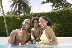Lyckliga föräldrar med sonen i simbassäng Royaltyfri Foto