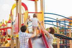 Lyckliga föräldrar med sonen som spelar på barn` s, glider royaltyfria bilder