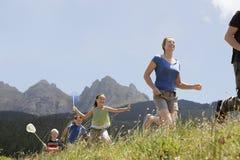 Lyckliga föräldrar och barn som kör till och med fält Arkivfoton