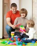Lyckliga föräldrar och barnspelrum med meccano Royaltyfri Fotografi