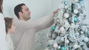 Lyckliga föräldrar och deras son som dekorerar julgranen i vardagsrummet fotografering för bildbyråer