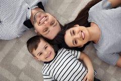 Lyckliga föräldrar och deras son som tillsammans ligger på golvet, sikt från över royaltyfri fotografi