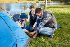 Lyckliga föräldrar och soninställning - upp tältet på campingplatsen royaltyfria foton