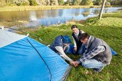 Lyckliga föräldrar och soninställning - upp tältet på campingplatsen fotografering för bildbyråer